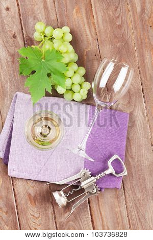 White wine glass and grapes on wooden table. Top view