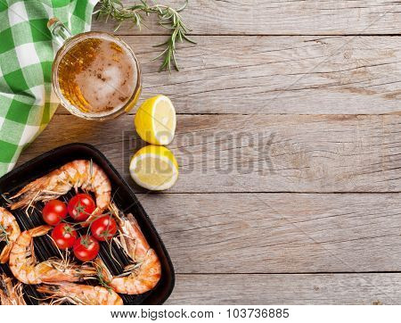 Grilled shrimps on frying pan and beer. Top view with copy space