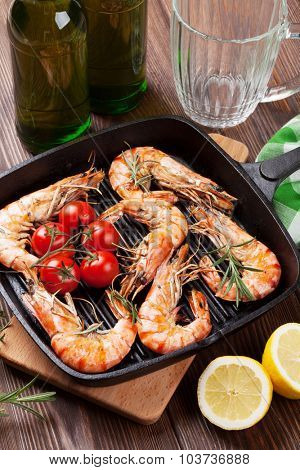 Grilled shrimps on frying pan and beer on wooden table