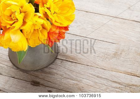 Colorful tulips bouquet in watering can on wooden table. Top view with copy space