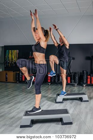 Couple doing exercises over steps in fitness center