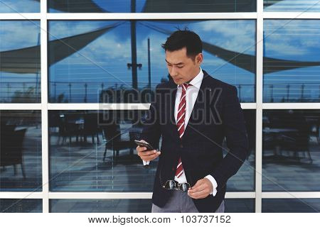 Young asian businessman holding his mobile phone while standing at office building window outdoors