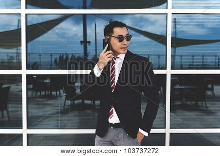 Young asian businessman talking on cellphone while standing near office window