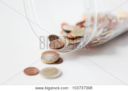 business, finance, investment, money saving and budget concept - close up of euro coins in glass jar on table