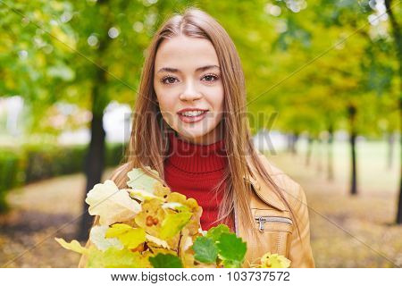Happy girl with oak leaves looking at camera in park