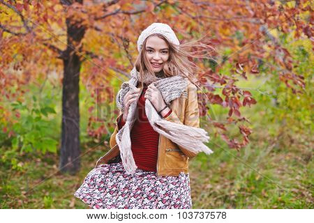 Stylish girl in leather jacket and knitted cap and scarf looking at camera in park
