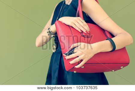 Fashionable beautiful big red handbag on a shoulder of the girl in a black dress trendy. Warm colors