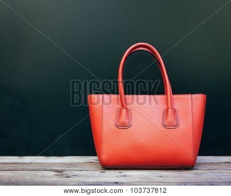 Fashionable beautiful big red handbag standing on a wooden floor on black wall background. Still lif