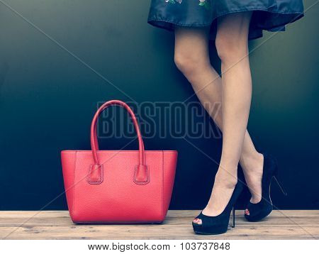 Fashion leggy girl in a beautiful high-heeled shoes in short denim dress summer posing near the dark