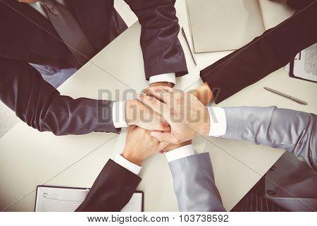 Hands of business partners on desk
