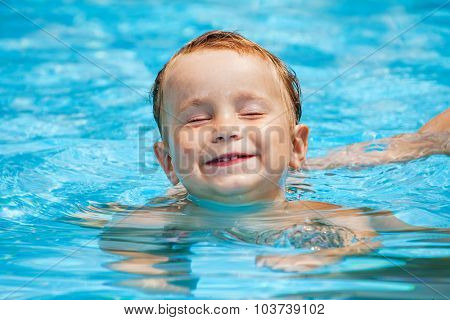 little boy in the swimming pool in hot day