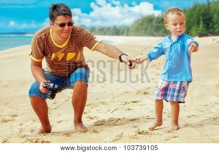 the son asked his father to take a picture of a crab on the beach