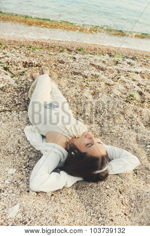 Young smiling female dressed in white clothing lying on a sea sand and listening music.