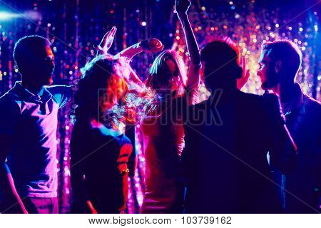 Group of guys and girls dancing in the night club