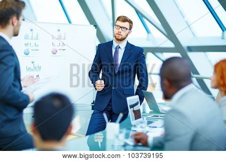 Young businessman looking at colleague while listening to his explanation
