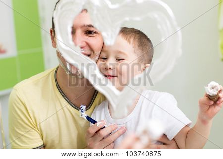 Father and child son drawing heart shape on mirror with shaving foam playing in bathroom