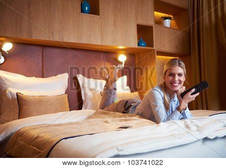 young business woman relaxing in hotel room and looking tv