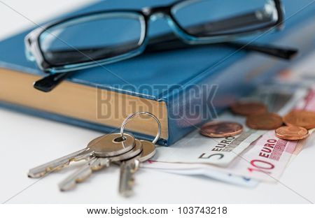 personal stuff and objects concept - close up of book, money, glasses and keys on table