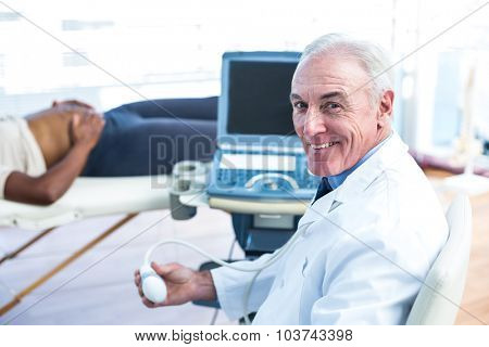 Portrait of smiling male doctor holding ultrasound in clinic