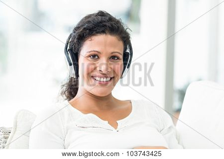 Portrait of happy pregnant woman with headphones sitting on sofa