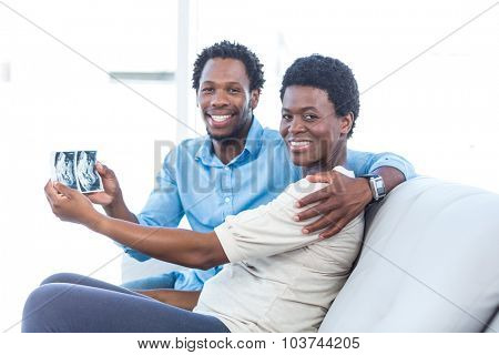 Portrait of happy couple showing photo while sitting at home
