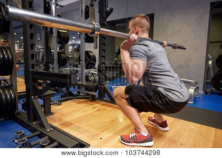 sport, fitness, bodybuilding, lifestyle and people concept - young man with bar of barbell flexing muscles in gym