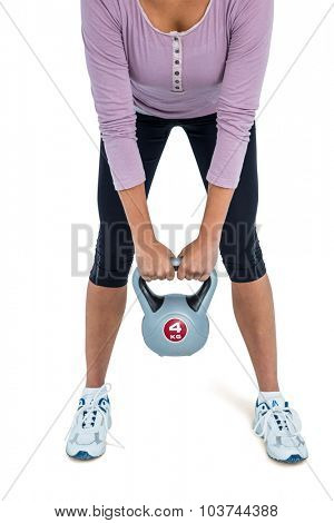 Low section of woman exercising with kettlebell over white background