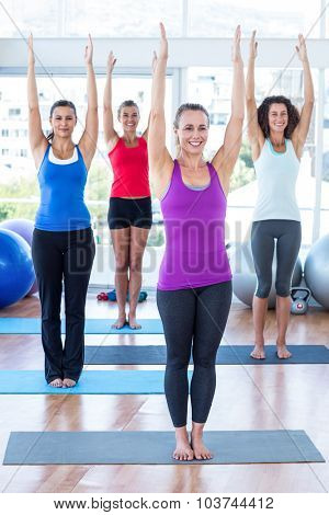 Happy women in fitness studio with arms raised while standing on exercise mat