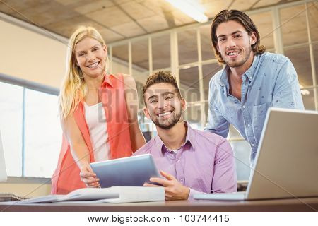 Portrait of stylish business people looking at digital table in creative office