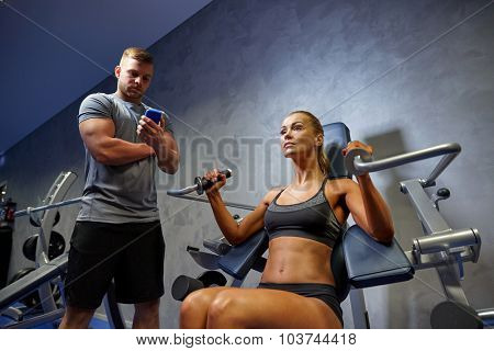 sport, fitness, bodybuilding, teamwork and people concept - young woman and personal trainer with smartphone flexing muscles on gym machine