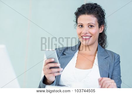 Portrait of smiling businesswoman using smart phone while working in office