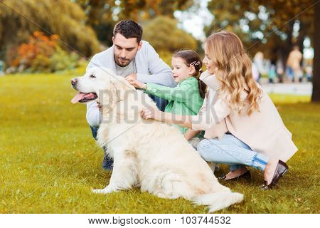family, pet, domestic animal, season and people concept - happy family with labrador retriever dog on walk in autumn park