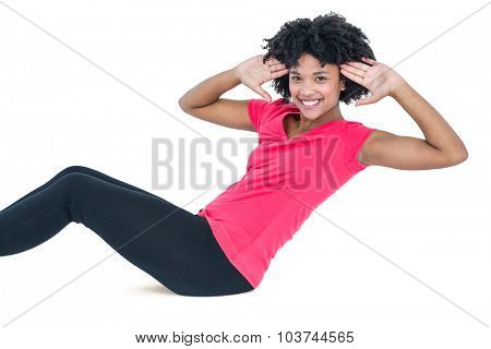 Portrait of young woman doing sit ups over white background