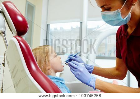 Pediatric dentist examining little girls teeth in the dentists chair