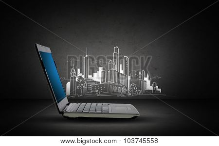 technology, electronics and advertisement concept - open laptop computer with blank screen and city sketch over dark gray background