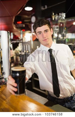 Portrait of male bartender serving beer at bar counter