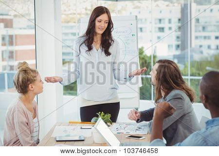 Woman gesturing while discussing with coworkers at office