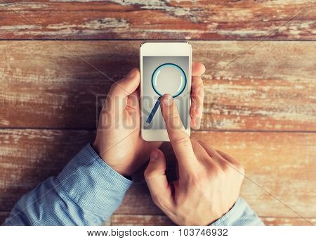 business, education, people and technology concept - close up of male hands holding smartphone with magnifying glass picture on screen at table