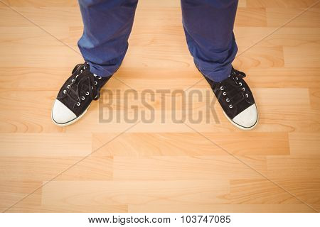 High angle view of man wearing canvas shoes standing on hardwood floor