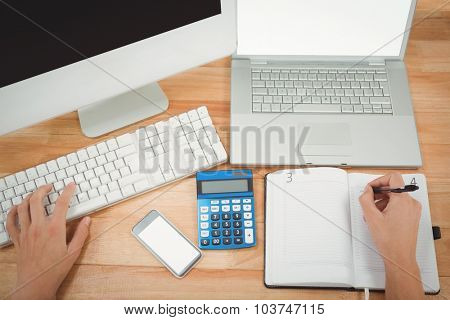 Cropped image of businessman writing on diary while using computer at desk in office