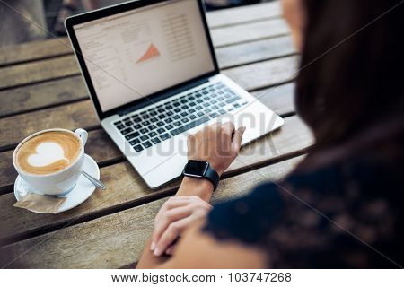 Woman In Cafe Using Latest Technology Devices