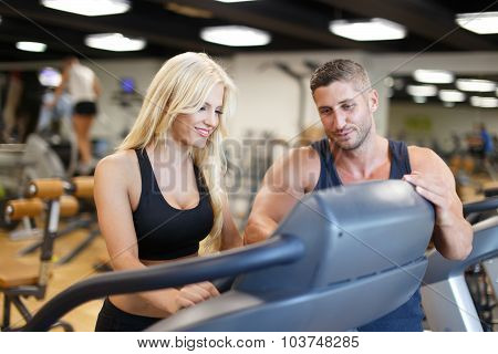 Personal Trainer Show Treadmill For Blonde Woman In Gym