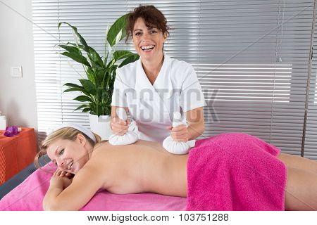 Woman Getting Thai Herbal Compress Massage In Spa.she Is Very Relaxed