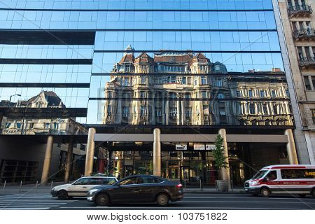 BUDAPEST, HUNGARY - SEPT 20, 2015: Traffic on the street in the historic centre of Budapest. The reflection of the ancient building in the Windows of a modern building.