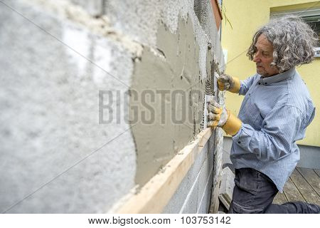 Builder Applying Tiles To A Wall