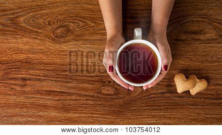 woman holding hot cup of tea with cookies on wooden table. Header for website