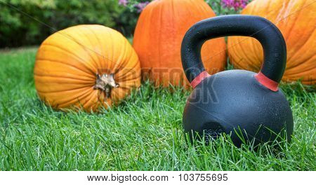 heavy iron kettlebell and  pumpkins in a backyard lawn - holiday fitness concept