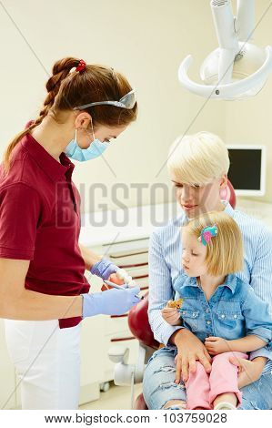 Pediatric dentist explaining to young patient and her mother the model