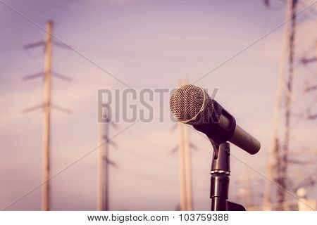 Microphone On A Stand With Blurred Electric Posts. Shallow Depth Of Field. Vintage Style And Filtere