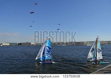 ST. PETERSBURG, RUSSIA - AUGUST 22, 2015: Helicopters with Russian flags over Extreme 40 catamarans during St. Petersburg stage of Extreme Sailing Series. The Day of Flag is celebrated in Russia today